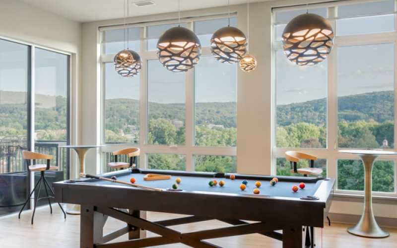 Pool table in clubhouse next to floor-to-ceiling windows and overhead pendant lights